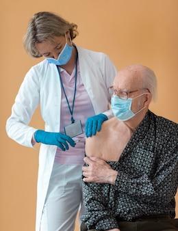 Mittelgroßer alter mann, der sich impfen lässt