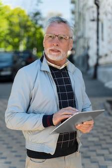 Mittelgroßer alter mann mit tablet