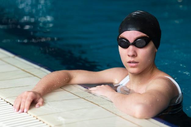 Mittelgroßer athlet, der mit kappe schwimmt