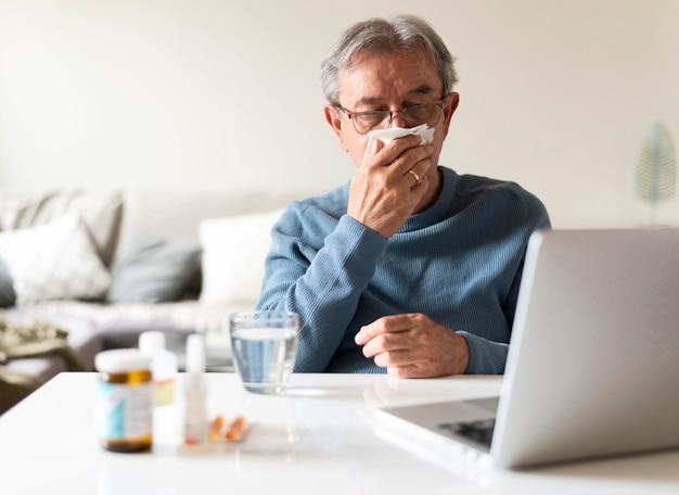 Mittelgroßer kranker mann mit laptop