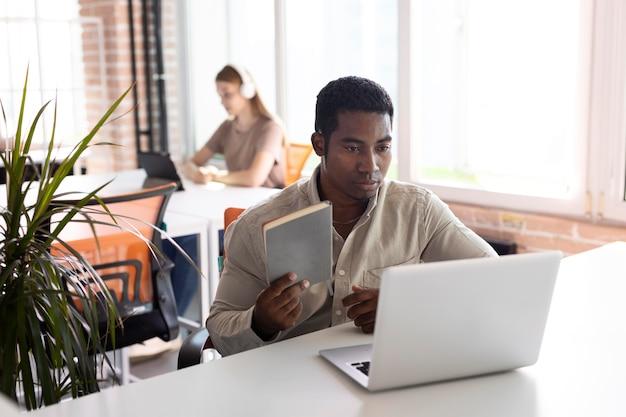 Mittelgroßer mann bei der arbeit mit laptop