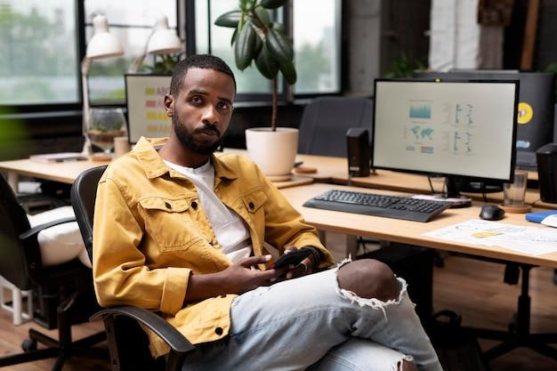 Mittelgroßer mann, der am schreibtisch sitzt