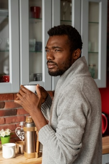 Mittelgroßer mann, der drinnen kaffee trinkt