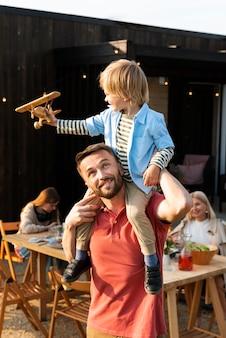 Mittelgroßer mann, der mit kind spielt