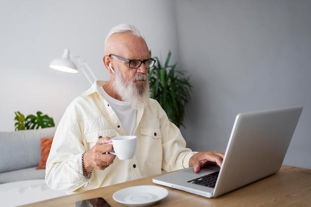 Mittelgroßer mann, der mit laptop studiert