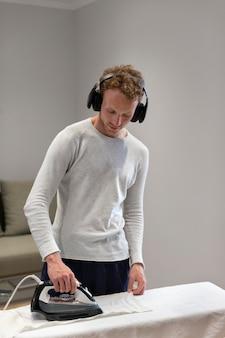 Mittelgroßer mann mit kopfhörer beim bügeln