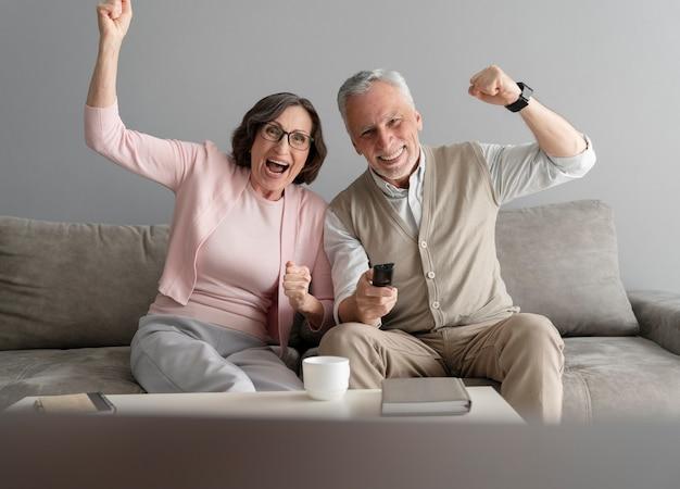 Mittelgroßes glückliches paar mit fernbedienung