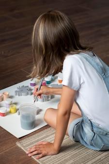 Mittelgroßes kind, das zu hause kreativ ist