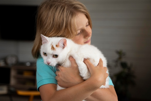 Mittelgroßes kind umarmt katze