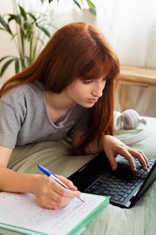 Mittelgroßes mädchen, das mit laptop arbeitet