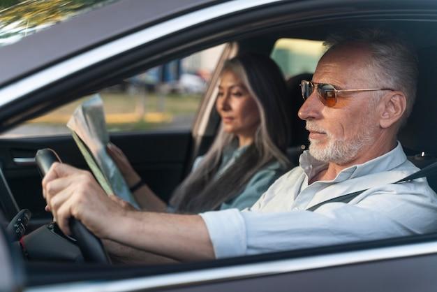 Mittelgroßes paar, das mit dem auto reist