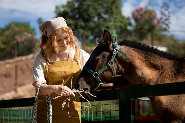 Mittelhohe frau, die pferd füttert