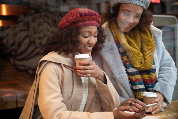 Mittelhohe frauen mit kaffeetassen