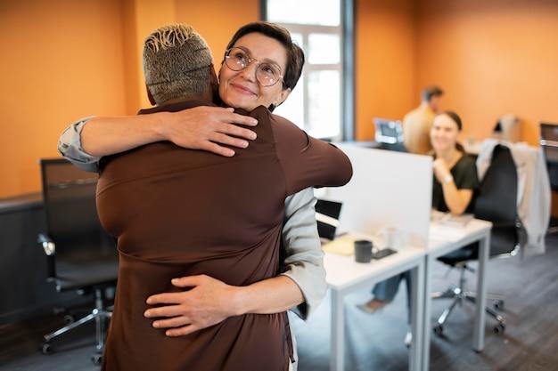 Mittelhohe leute, die sich bei der arbeit umarmen