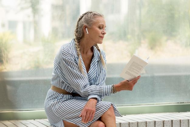 Mittelhohe seniorin, die ein buch liest