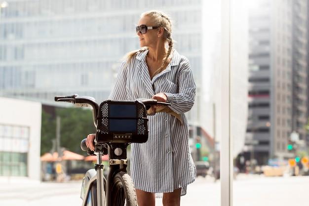 Mittelhohe seniorin mit fahrrad