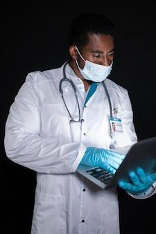 Mittelhoher arzt mit laptop
