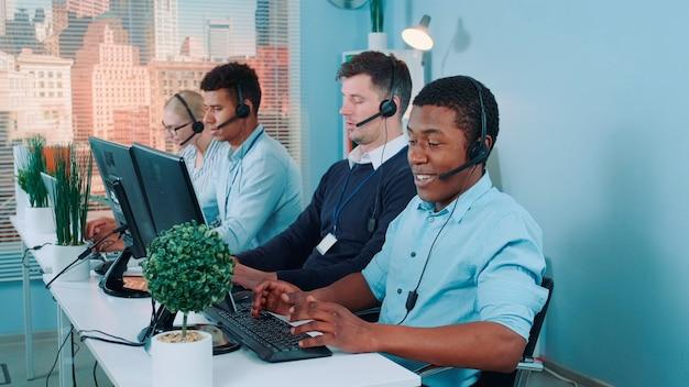 Mittellange aufnahme eines schwarzen kundendienstmitarbeiters, der in einem geschäftigen callcenter arbeitet, indem er mit dem inter...