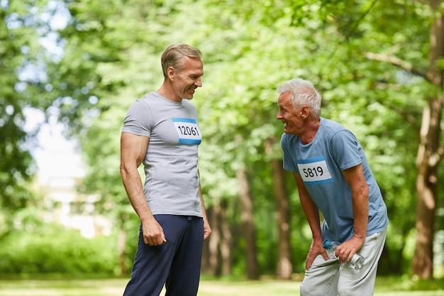 Mittellange porträtaufnahme von zwei älteren männern, die am sommermarathonrennen teilnehmen und zusammen stehen und über etwas sprechen