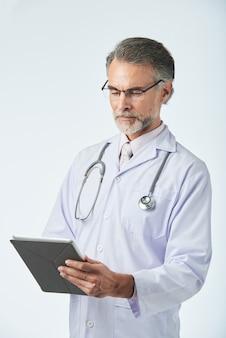 Mittellanger schuss von doktor von mittlerem alter, der mit digitaler tablette arbeitet