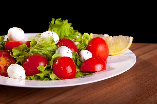 Mittelmeergemüsesalat mit käsebällen und zitrone, tomaten, grüns, auf einem holztisch und einem schwarzen hintergrund.