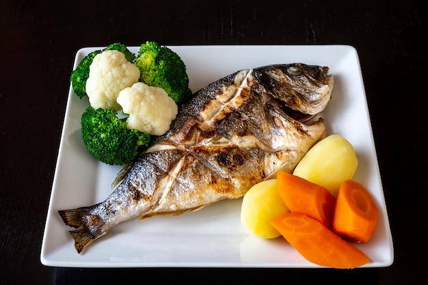Mittelmeergericht, sparus aurata aus gebackenem fischgemüse und salzkartoffeln. gesundes essen.
