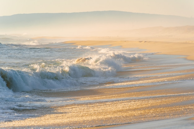 Mittelmeerkosten bei sonnenuntergang. tropisches inselufer mit starken stürmischen wellen in bewegung. sonnenlicht auf gelbem sand jenseits des ozeans. paradies malerische seelandschaft.