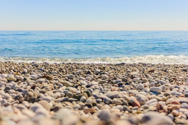 Mittelmeerlandschaft in antalya, die türkei. blaues meer, wellen und kieselstrand