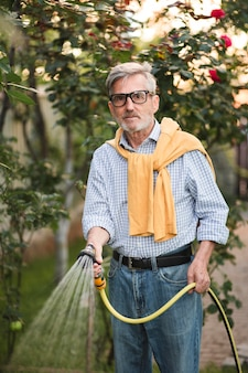 Mittelschuss alte mann, der pflanzen gießt