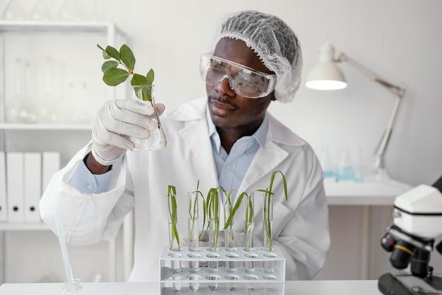 Mittelschuss-forscher, der pflanze hält