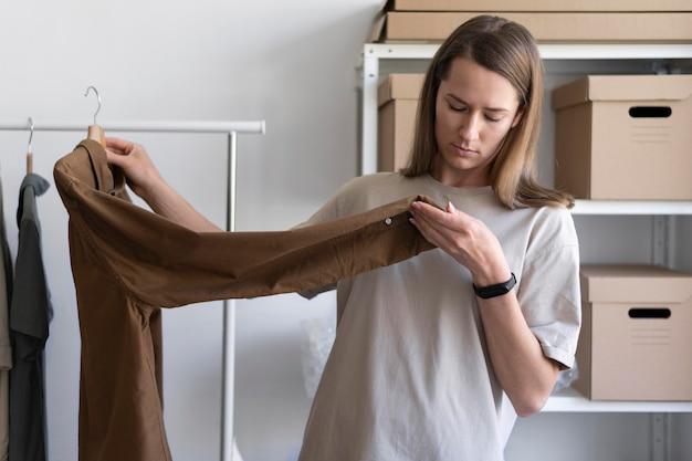 Mittelschuss-geschäftsfrau, die hemd prüft