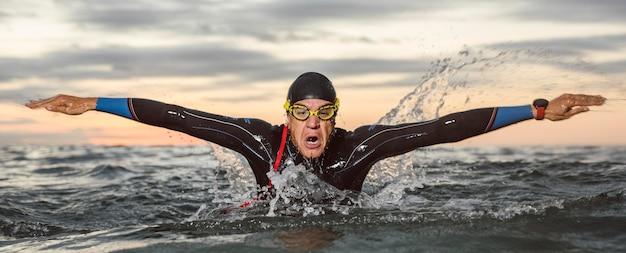 Mittelschuss mann, der vorderansicht schwimmt
