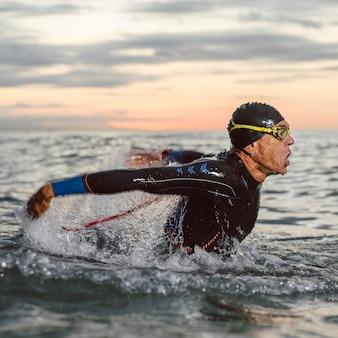 Mittelschuss mann schwimmende seitenansicht
