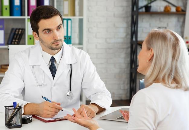 Mittelschussarzt spricht mit dem patienten