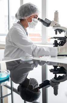 Mittelschussforscher, der mit mikroskop arbeitet