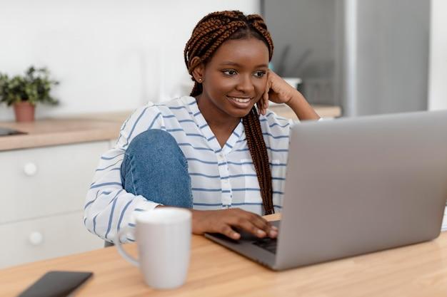 Mittelstarke frau mit laptop zu hause