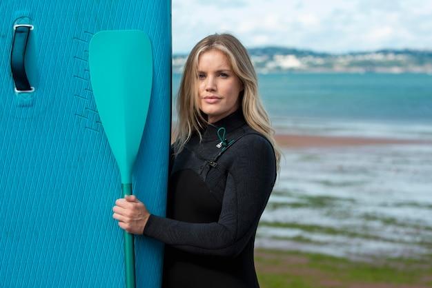 Mittelstarke frau mit paddleboard