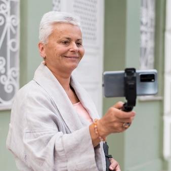 Mittelstarke frau mit selfie-stick