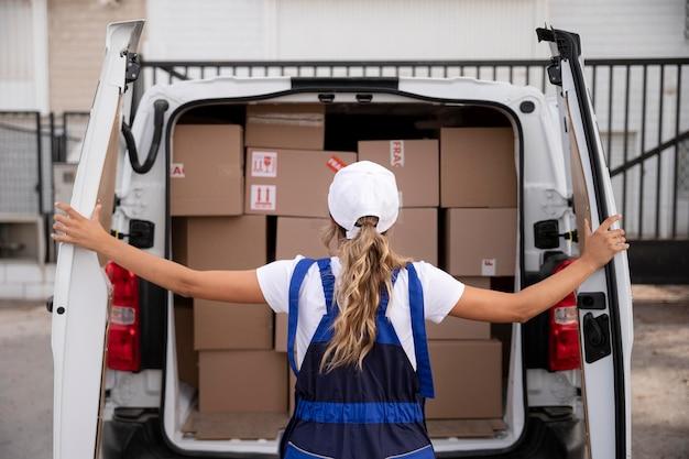 Mittelstarke lieferfrau mit lieferwagen