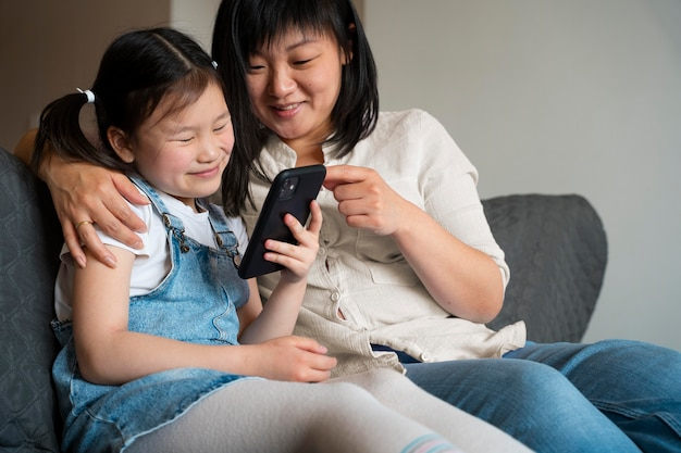 Mittelstarke mutter und kind mit telefon