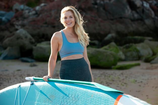 Mittelstarke smiley-frau mit paddleboard