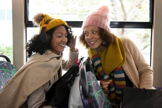 Mittelstarke smiley-frauen, die mit dem bus reisen