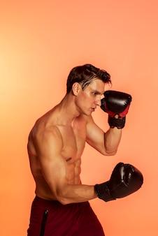 Mittelstarker mann beim training mit boxhandschuhen