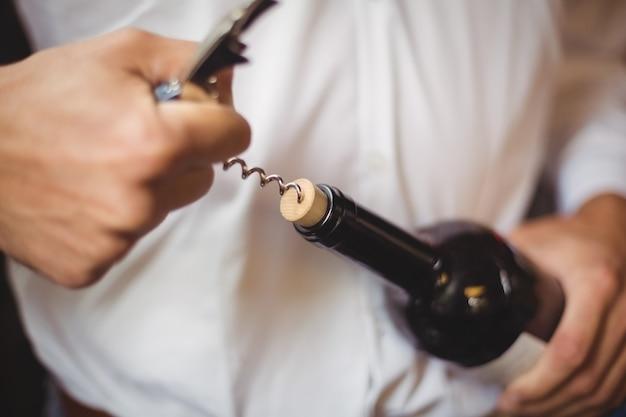 Mittelteil der bar tender öffnet eine flasche wein