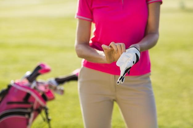 Mittelteil der frau, die golfhandschuh trägt