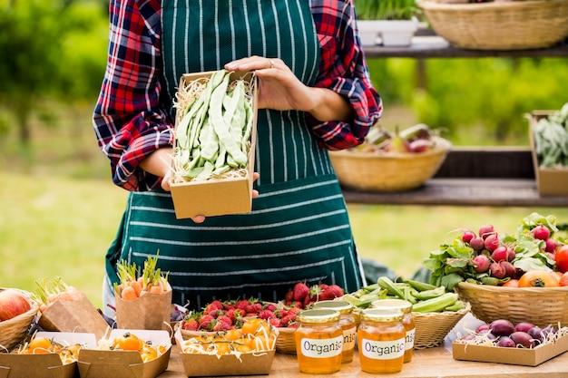 Mittelteil der jungen frau organisches gemüse verkaufend