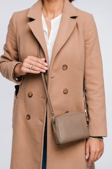 Mittelteil der jungen stilvollen frau im eleganten beigen mantel mit der kleinen lederhandtasche, die isoliert steht