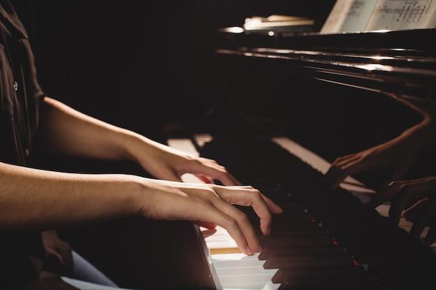 Mittelteil der studentin, die klavier spielt