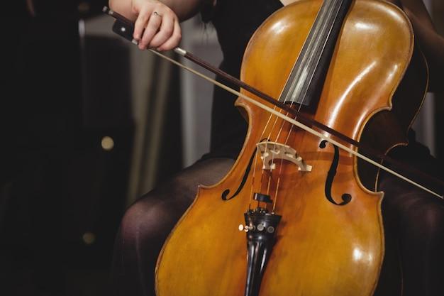 Mittelteil der studentin, die kontrabass spielt