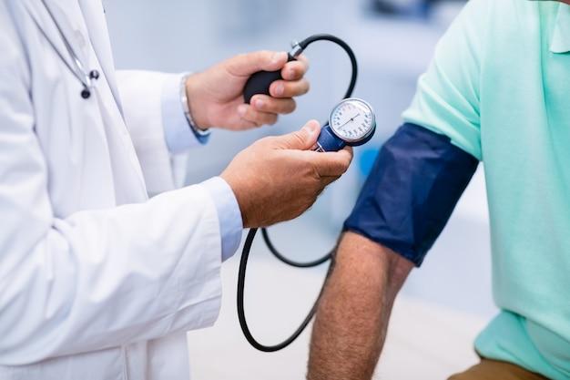 Mittelteil des arztes, der den blutdruck eines patienten überprüft